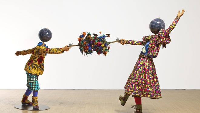 """Yinka Shonibare's """"Flower Power Kids"""" are built from globes, batik clothes and stunt pistols that """"shoot"""" bouquets of fake flowers."""