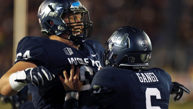 Wolf Pack center Sean Krepsz celebrates with quarterback Ty Gangi after a touchdown against Hawaii last season.