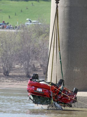 A  vehicle that plunged from the I-275 Combs-Hehl Bridge into the river 3/15 after being hit during an accident is lifted from the river by a crane.  Authorities confirmed one body was in the vehicle.