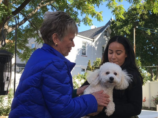 Irma Santiago Karpyszyn and Aryana Velez enjoy their dog, Linda, after it was returned on Wednesday eight months after being taken by theft.