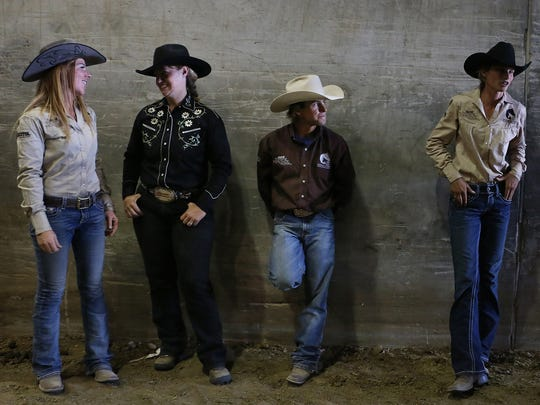 Horse trainer Kirk Ferris, middle right, waits back stage with fellow competitors during the Extreme Mustang Makeover event at the Reno Rodeo on June 19, 2016.
