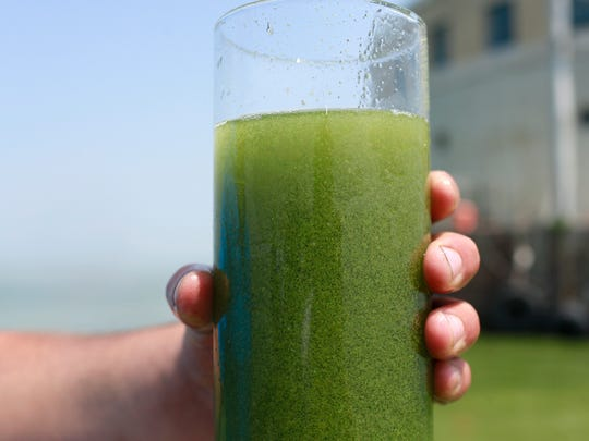 A sample glass of Lake Erie water is photographed Aug. 3, 2014, near the City of Toledo water intake crib on Lake Erie, off the shore of Curtice, Ohio. Researchers and officials across the country say increasingly frequent toxic algae blooms are another bi-product of global warming. They point to looming questions about their effects on human health.