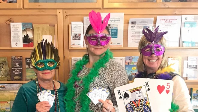 Decked out in the best Mardi Gras attire, Chamber staffers, from left, Penny Utley, Randi Morrow and Laurie Findley encourage community members to share in their celebration on Saturday at the Deming-Luna County Chamber of Commerce Party Gras event at the Mimbres Valley Special Events Center.