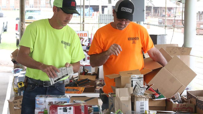 Berry McHenry, left, and Billy Smith pick up some small clamps for the job, Friday, July 10, 2020, at the GetRDunn pre-auction sale at the Hugh Hardin Arena in Kay Rodgers Park. Tim Dunn, owner, will hold a public auction for items ranging from boxes of screws and tools to salvaged and wholesale products, Saturday, July 11, 2020, at 10 a.m. in the arena.