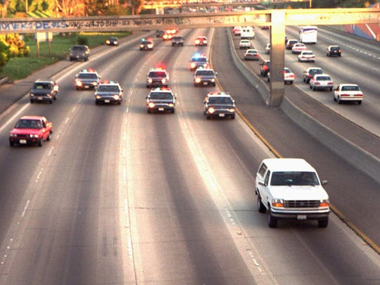 "White Ford Bronco driven by Al ""A.C."" Cowlings and carrying O.J. Simpson trailed by police cars on freeway"