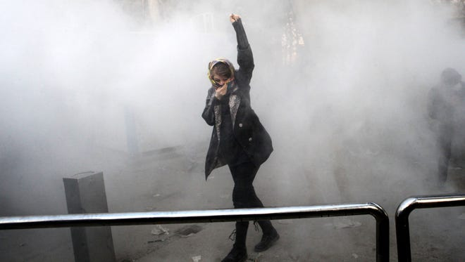 An Iranian woman raises her fist amid tear gas at the University of Tehran during a protest driven by anger over economic problems on Dec. 30, 2017.