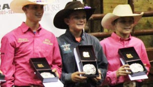 Dario Ceresola (center) of Fernley stands with the third place buckle he won in the goat tying event during the National Jr. High School Finals Rodeo in Iowa earlier this summer.