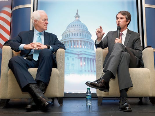 "U.S. Senator John Cornyn, R-Texas, left, listens as U.S. Rep. Beto O'Rourke, D-Texas, talks about immigration at the ""State of Congress"" hosted by the Greater El Paso Chamber of Commerce in April 2015."