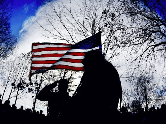 In this 2013 photo, Mark Day salutes the flag Ed Dowd is holding at the Woolson Monument before the start of the 57th Annual Remembrance Day Observance in Gettysburg.