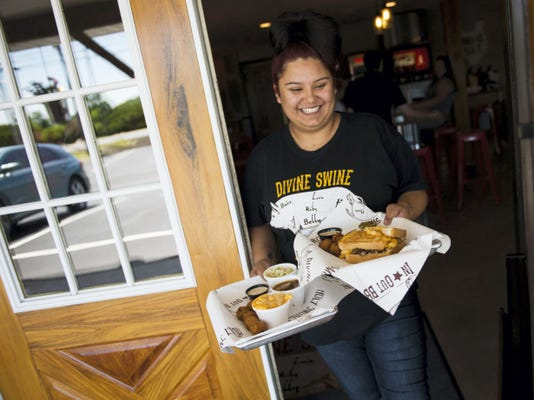 Amber Faust, a server at Divine Swine In & Out BBQ in Rapho Township, brings food to customers during lunch hour earlier this week. The restaurant expects to see an increase in business from fans attending the 2015 U.S. Women's Open at Lancaster Country Club.