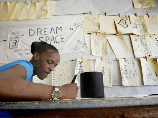Layla Murray of York City writes her dreams Monday in Spaceship York's Dream Space. The exhibit welcomes creative contributions from visitors at 9 W. Market St. from 9 a.m. to 2 p.m. Mondays, Tuesdays and Thursdays; from 6 to 9 p.m. Fridays; and from 10 a.m. to 2 p.m. Saturdays.