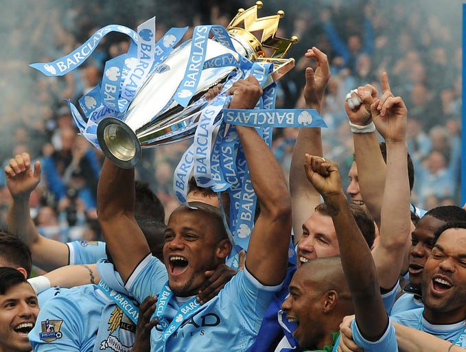 Manchester City's captain Vincent Kompany, center, holds the Cup and celebrates with team mates after being crowned Premier League  Champions, after the English Premier League soccer match between Manchester City and West Ham United at the Etihad Stadium,  Manchester, England, Sunday, May 11, 2014.