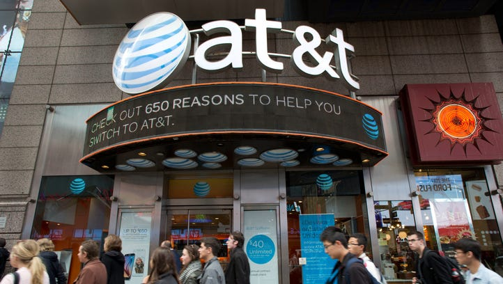 People walk by an AT&T retail store Oct. 24, 2016, in New York. AT&T plans to buy Time Warner for $85.4 billion.