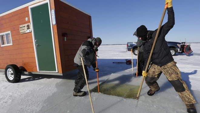 Lonny Ziemer of Rod-Bender Guide Service in Kaukauna and Paul Lueck of Fond du Lac sink a block of ice Thursday to open up a sturgeon hole on Lake Winnebago near Oshkosh.
