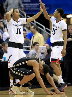 Cincinnati guard Troy Caupain, left, congratulates teammate Kevin Johnson after Purdue forward Vince Edwards, bottom, missed a last-second shot during overtime of an NCAA tournament second round college basketball game in Louisville, Ky., Thursday, March 19, 2015. Cincinnati won 66-65.