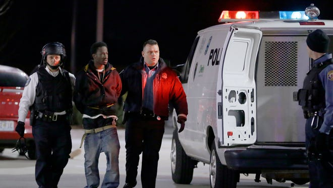 Police take a person into custody in Brentwood, Mo., during disturbances related to the situation in nearby Ferguson.