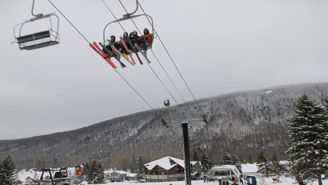 A group of skiers travel uphill on the ski lift at Bristol Mountain.