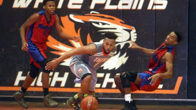 Spring Valley's Michael Maynes was called for the could while battling Peekskill's Charles Redd for the loose ball during a varsity basketball game at the Harvey Jefferson Showcase at White Plains High School Dec. 10, 2016. Spring Valley defeated Peekskill 77-58.