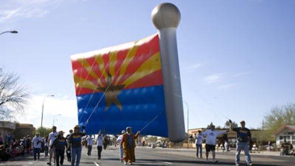 A huge Arizona Flag Balloon floats down Scottsdale Road at the Parada del Sol Parade