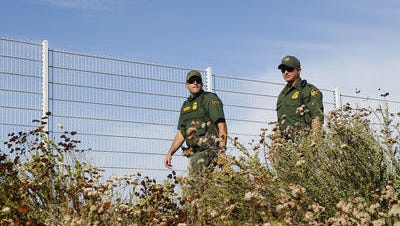 Border Patrol agents keep an eye on a immigration demonstration outside the Border Patrol facility Friday, July 4,, 2014 in Murrieta, California. A second busload of migrant families is expected to arrive.
