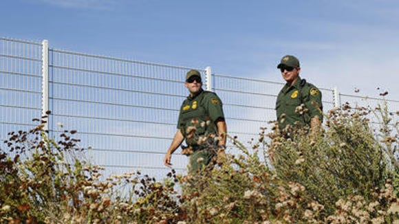Border Patrol agents keep an eye on a immigration demonstration