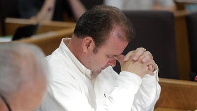 Brown County Supervisor Patrick Evans bows his head in prayer at the start of the County Board meeting on Wednesday, June 20, 2018. He was among the board majority who voted down a proposal to eliminate the prayer in favor of a 'moment of reflection.'
