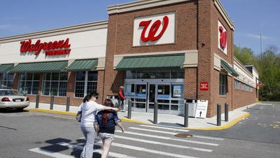 In this Wednesday, May 14, 2014 photo, customers walk toward an entrance to a Walgreen's store location, in Boston. Walgreen says its fiscal third quarter earnings jumped 16 percent compared with last year, helped in part by a lower income tax rate, but the nation's largest drugstore chain missed Wall Street's expectations.