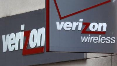 This June 4, 2014 photo shows signage at a Verizon Wireless retail store at Downtown Crossing in Boston. Verizon is reporting that its second-quarter earnings nearly doubled after securing full ownership of Verizon Wireless.