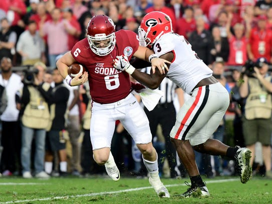Baker Mayfield looks to avoid a sack by linebacker