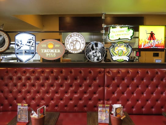 Lighted beer signs form a partial wall between the