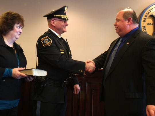 Mayor James R.  Barberio congratulates acting Parsippany Police Chief Paul Philipps after he was sworn in as permanent chief at council chambers in the Parsippany municipal building. Philipps wife, Grace look on, holding the bible. March 28, 2013.