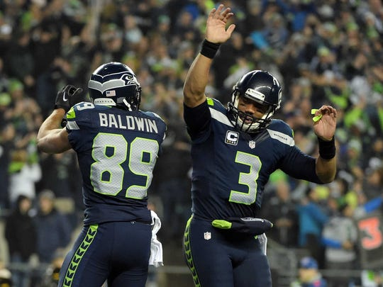 Seattle Seahawks wide receiver Doug Baldwin, left, celebrates with quarterback Russell Wilson after catching a touchdown pass against the Carolina Panthers during the first half in the 2014 NFC Divisional playoff football game Jan. 10.