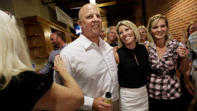 Rep. Scott DesJarlais, R-Tenn., and his wife, Amy, second from right, are cheered after he was declared the winner of Tennessee's 4th Congressional District primary race Thursday, Aug. 7, 2014, in South Pittsburg, Tenn.