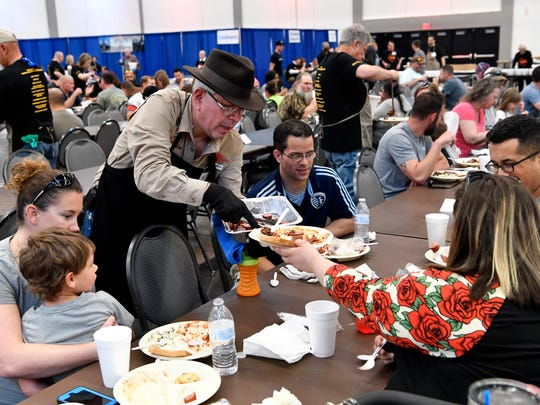 Ezequiel Casiano, a volunteer at the 53rd World's Largest Barbecue at the Abilene Convention Center, refills plates with sausage. Saturday's event was open to military members and their families.