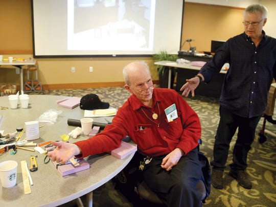 Charles O' Hara of Poulsbo demonstrates the mobility-impaired persons call button he made to instructor Curt Johnson from the University of Washington, an assistive technology specialist.