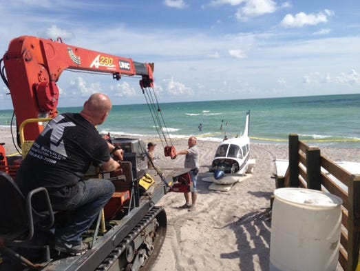 Workers prepare to remove the crashed plane from Caspersen Beach in Venice.