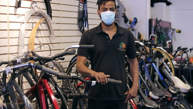 In this Wednesday, June 24, 2020, photograph, Noah Hicks, owner of Spokehouse Bikes in the Upham's Corner neighborhood of Boston, poses at his shop. Many from outside Boston have donated to and shopped at the store which was robbed and vandalized earlier in the month.