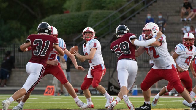 Shawnee Heights senior quarterback Hunter Wohler loads up to throw in the pocket. Shawnee Heights fell during their season opener against Lawrence High School 53-0 Friday night.