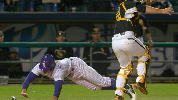 LSU's Andrew Stevenson scores as Southern Miss' Austin Roussel reaches for the throw Tuesday at Zephyr Field in Metairie, La.