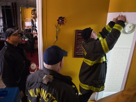 Wilmington Firefighter EJ Castagna, right, installs