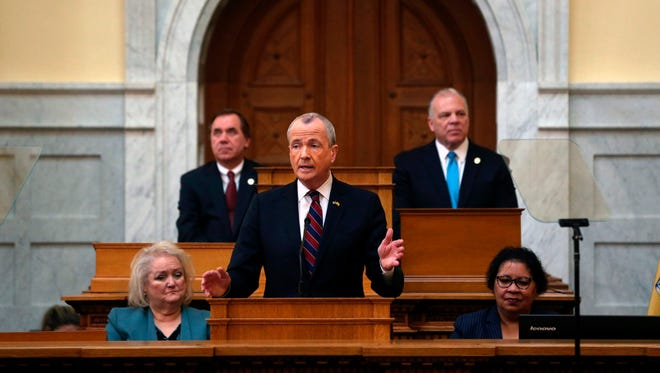 FILE - In this March 13, 2018 file photo, As New Jersey Assembly Speaker Craig J. Coughlin, back left, D-Woodbridge, N.J., and Senate President Steve Sweeney, back right, D-West Deptford, N.J., listen as New Jersey Gov. Phil Murphy, center, addresses a gathering as he unveils his 2019 budget  in the Assembly chamber of the Statehouse in Trenton, N.J. Murphy and  Sweeney are both Democrats, but their disagreements, most recently a race-infused clash over confirming Cabinet officers, hints at trouble among two key figures responsible for enacting New Jersey's roughly $37 billion budget.