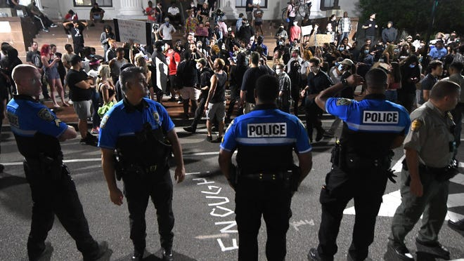 Officers with the Wilmington Police Department stand along Third Street. during a protest in support of George Floyd at Wilmington City Hall in downtown Wilmington, N.C., Monday, June 1, 2020.