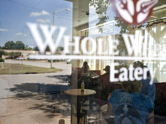 The scene outside the restaurant is reflected in the glass as patrons enjoy their lunch at the Whole Wheatery Eatery in this Advertiser file photo. The restaurant and health food store in the Oil Center will be closing its doors next month after more than 40 years in business.