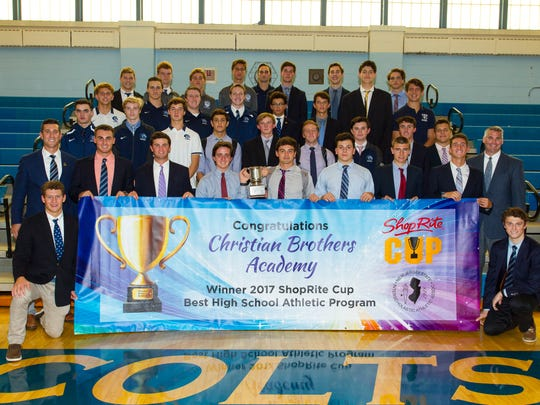Picture One is Director of Athletics Vito Chiaravalloti (left) and Principal Ross Fales (right) with members of each varsity team at CBA.