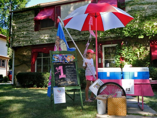 Lili Malone, 8, helps set up her Lili's Ice Cream Stand