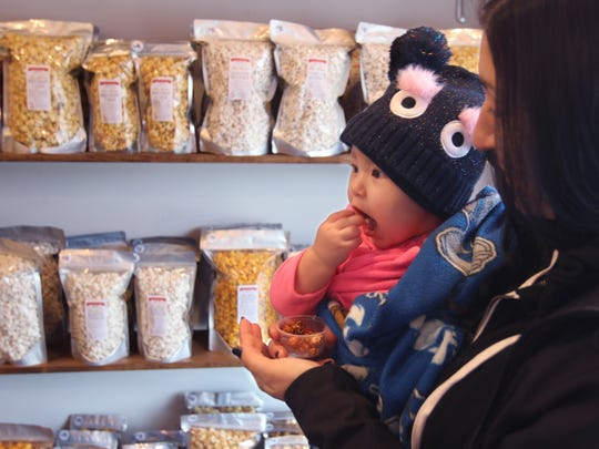 Adeline Jenkins, 1, samples some of the flavored popcorn