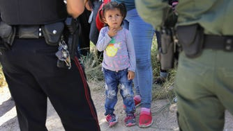 A Mission Police Dept. officer , left, and a U.S. Border Patrol agent watch over a group of Central American asylum seekers before taking them into custody on June 12, 2018, near McAllen, Texas.