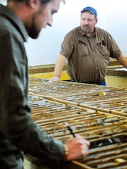 Jerry Zieg, vice president of exploration for Tintina Resourses Inc., and Kevin Gostomski, with Tintina, log core samples measurements of ore taken from a potential underground copper mining site that Tintina hopes to develop located on privately owned ranchland between White Sulphur Springs and Neihart.