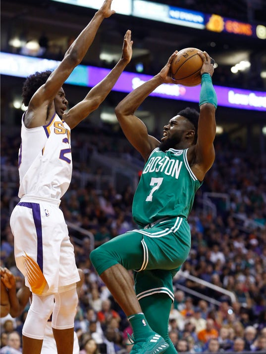 Boston Celtics guard Jaylen Brown (7) tries to drive past Phoenix Suns guard Josh Jackson, left, during the first half of an NBA basketball game Monday, March 26, 2018, in Phoenix. (AP Photo/Ross D. Franklin)
