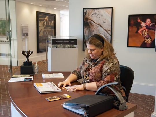Tamora Kowalski working at her job at the Biggs Museum of American Art in Dover on Nov.14, 2014, while her husband Jake is at the Dover Public Library studying for his certified public accountants test.